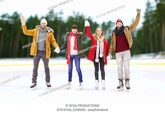 happy friends waving hands on outdoor skating rink