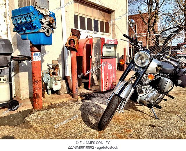 A motorcycle in front of an abandoned gas station