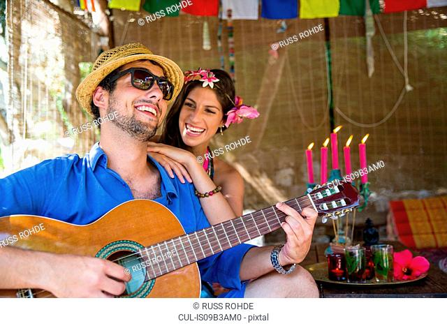 Young couple playing guitar smiling
