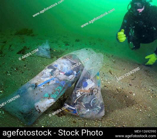 Diver observes bags full of garbage on the seabed. Plastic materials under the mechanical and chemical action of sea water degrade rapidly by disintegrating...