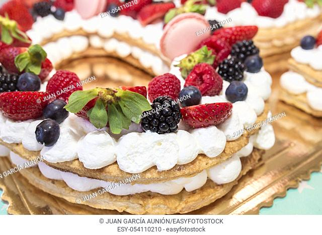 Fruits of the forest cake with cream and pastry. Closeup