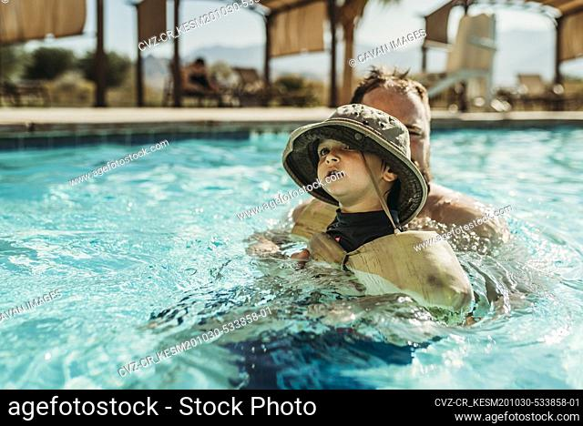Close up of young toddler boy and father swimming in pool on vacation