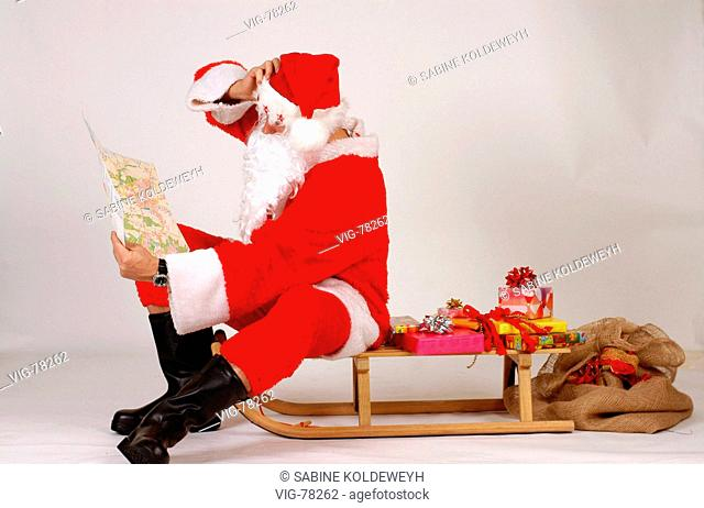 Santa Claus sitting on a sledge and looking on a map. - GERMANY, 08/12/2004