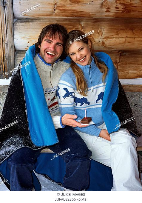 Couple wrapped in blanket with cake and candle