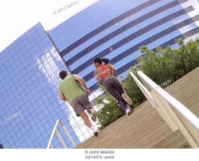 Man and woman running up stairs, rear view tilt
