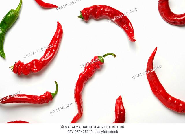 many red whole fruits of hot pepper and one green on a white background, close up