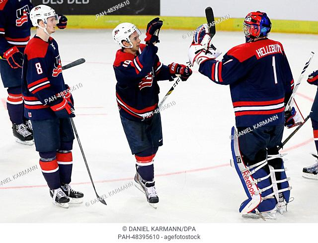 USA's Jacob Trouba (L-R), Tim Stapleton and Connor Hellebuyck cheer after the 1-3 victory in the ice hockey world cup friendly match between Germany and USA at...