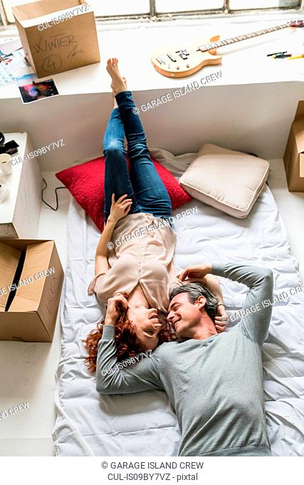 Couple moving into apartment, lying face to face on mattress, overhead view