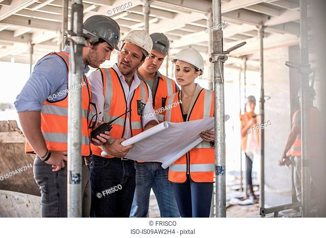 Four female and male builders with blueprint on construction site