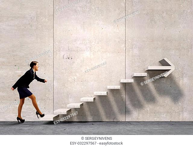 Businesswoman in suit stepping up stone staircase