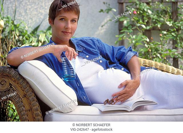 portrait, half-figure, outdoor, pregnant woman with short brown hair wearing a white dress and a jeans shirt relaxing with a book on a cane sofa in the garden...
