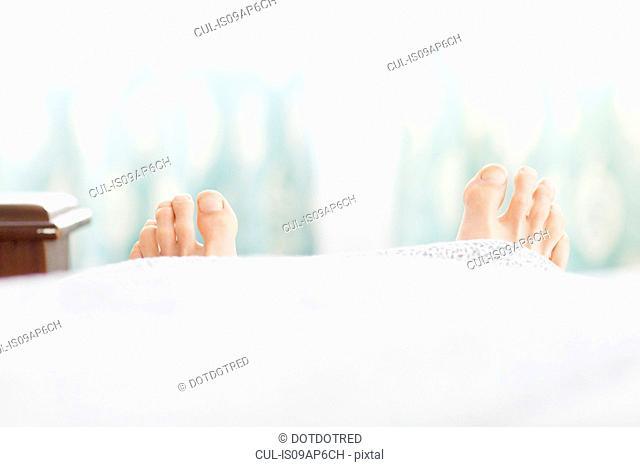Pair of feet sticking out under duvet