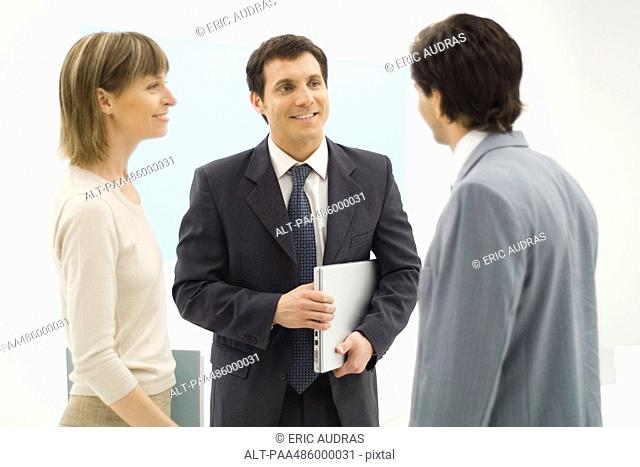 Three business associates standing, talking together, smiling