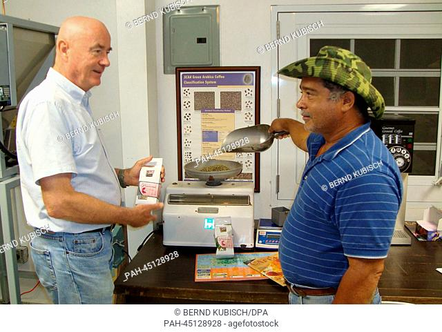 Kurt Legner (L)and one of his employees weigh coffee beans at the Legner family farm in Las Carmelitas, Puerto Rico, 07 January 2013
