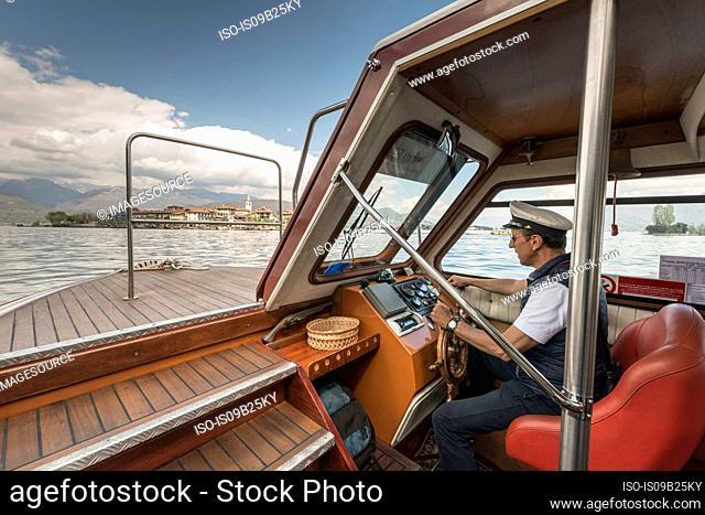 Captain driving tour boat, Lago Maggiore, Isole Borromee, Isola dei Pescatori, Borromean Islands