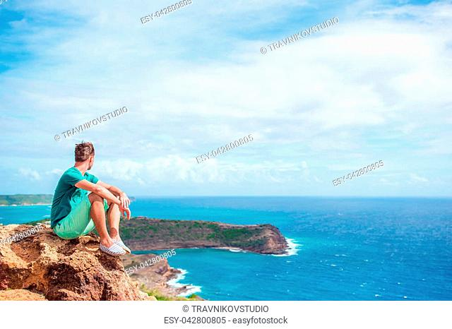 Young man enjoying breathtaking views from Shirley Heights on Antigua island