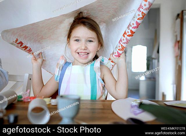 Portrait of happy little girl tinkering with paper