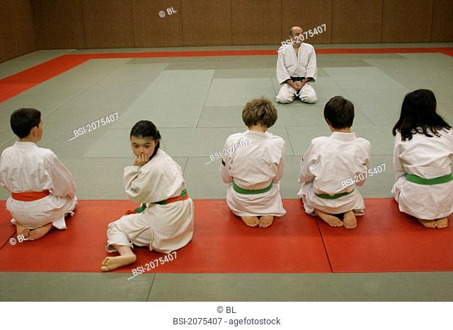 14-year-old teenager girl with down's syndrome during a judo class with other valid children