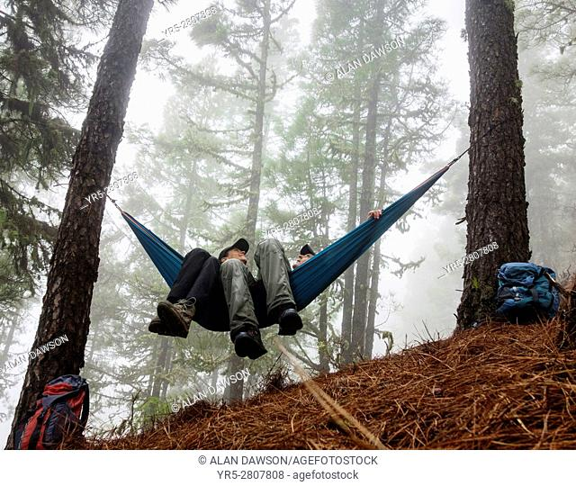 Mature couple in hammock in misty forest in mountains of Gran Canaria, Canary Islands, Spain. Model Released