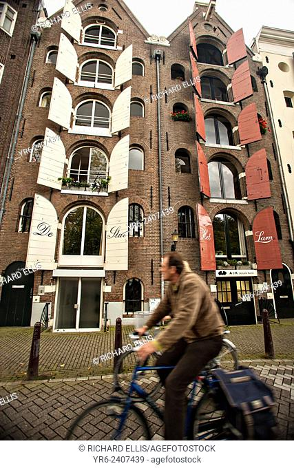 Bicyclist a house with white and red shuts in Amsterdam