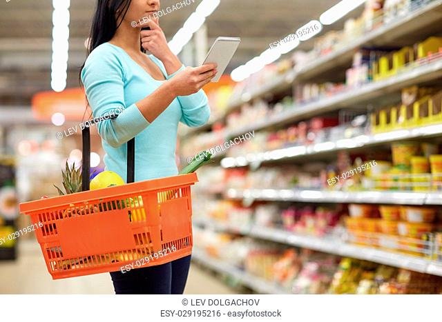 consumerism and people concept - woman with notebook and shopping basket buying food at grocery store or supermarket