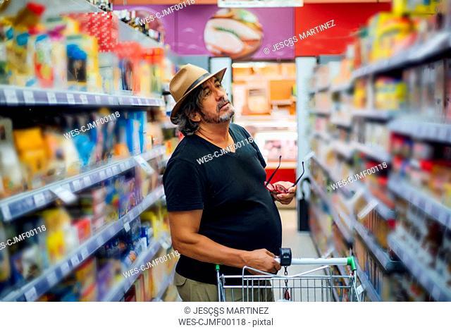 Senior man shopping in a supermarket