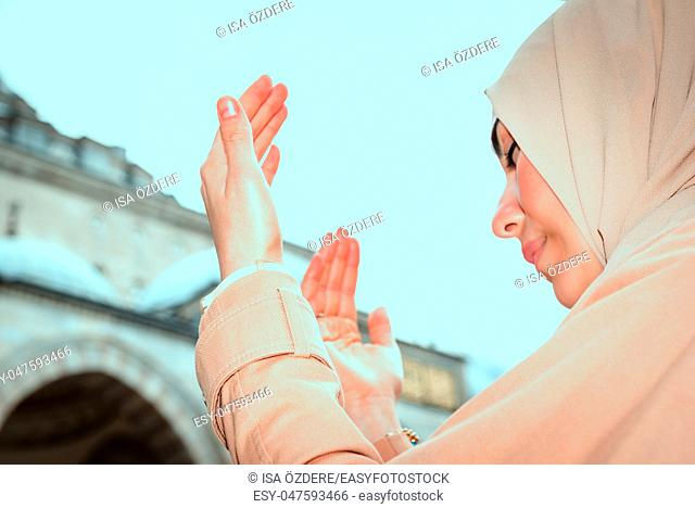 Muslim woman in headscarf and hijab prays with her hands up in air with mosque at background. Religion praying concept