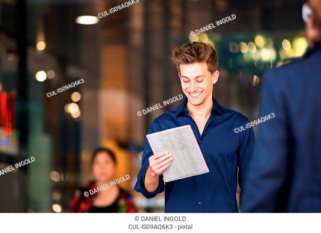 Young man strolling in shopping mall reading digital tablet