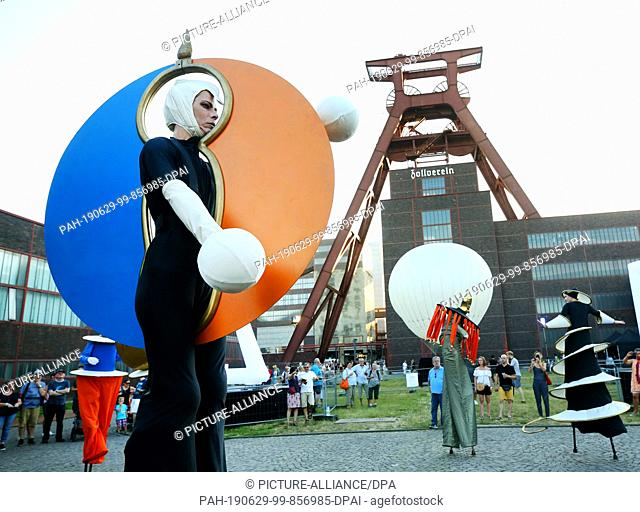 29 June 2019, North Rhine-Westphalia, Essen: Imaginatively costumed actors on stilts walk across the site during the extra shift at the Zollverein colliery