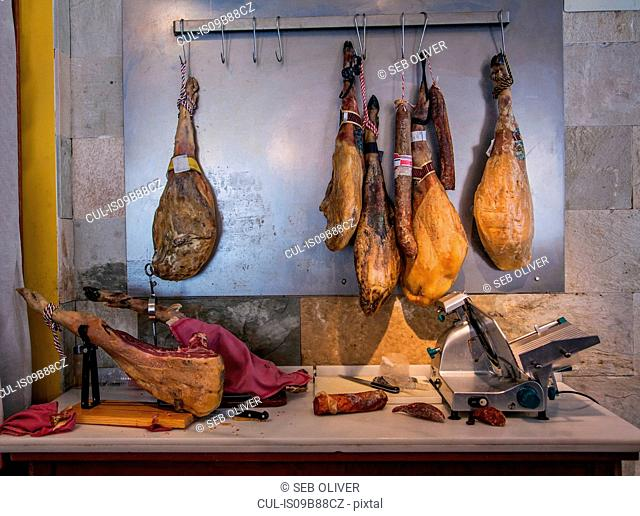 Iberico Ham hanging from meat hooks above kitchen counter, Catalonia, Spain