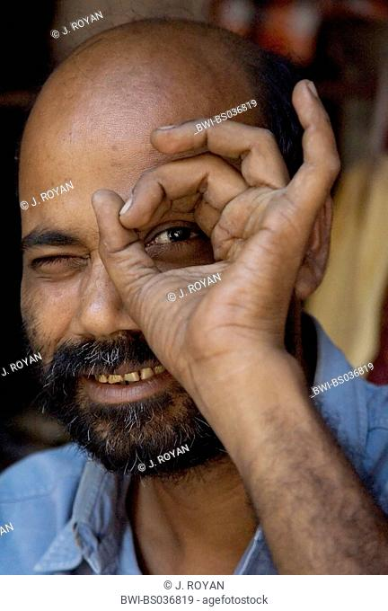 man peeking through a hole formed with his thumb and index finger, India, Varanasi