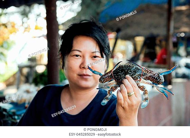 Asian woman plump body holding a fresh raw sea flower crab (portunus pelagicus) premium grade display for sale at seafood market