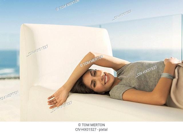 Portrait smiling woman relaxing laying on chaise lounge