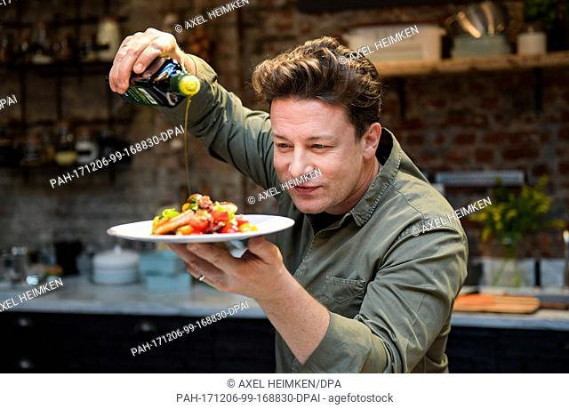 """The British chef Jamie Oliver cooks at the One Kitchen Culinary School in Hamburg, Germany, 6 December 2017. Oliver also presented his book """"""""5 Ingredients ·..."""