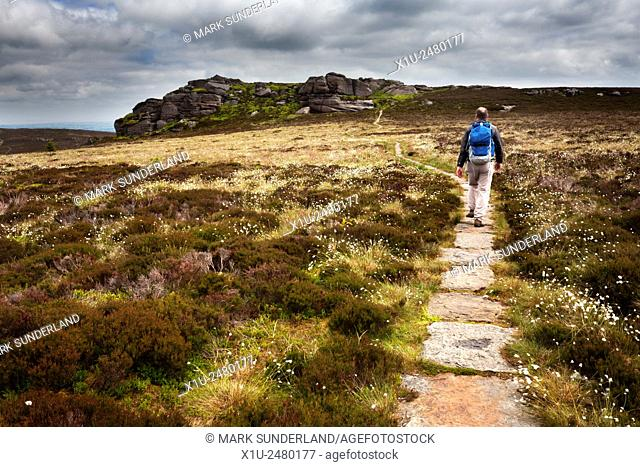 Walker on the Path approaching Old Stell Crag in the Simonside Hills near Rothbury Northumberland England