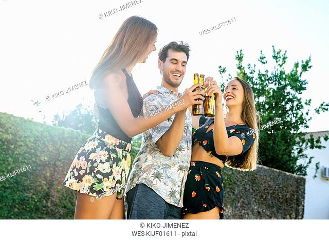 Friends toasting with beer bottles outdoors