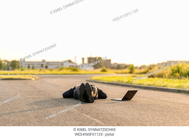Businessman lying on a road next to laptop