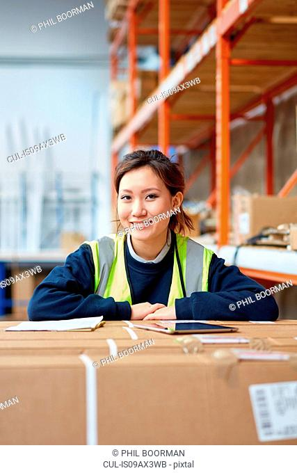 Portrait of female factory worker in factory warehouse