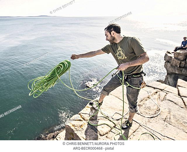 Man throwing rope as climbers preparing to climbing on Otter Cliffs, Acadia National Park, Maine, USA