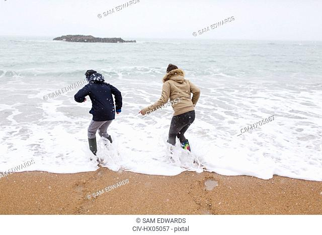 Playful teenage brother and daughter playing in winter ocean surf