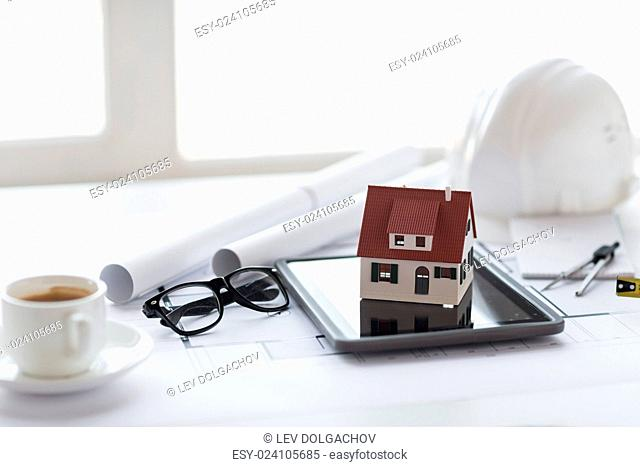 architecture, building, construction, real estate and home concept - close up of living house model on tablet pc computer screen at office