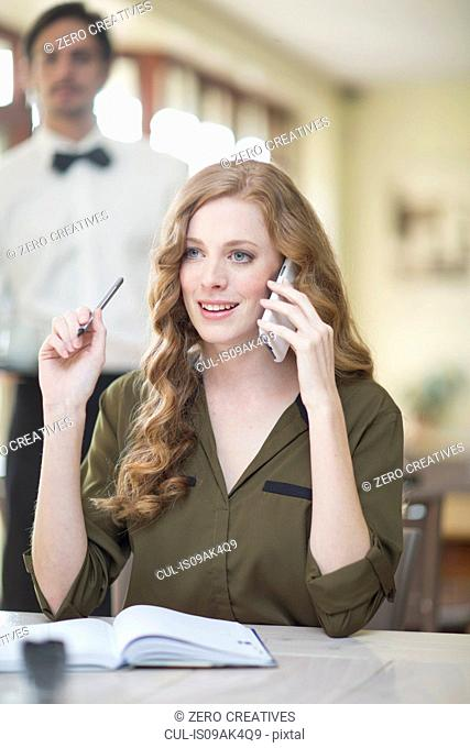 Young businesswoman chatting on smartphone in restaurant
