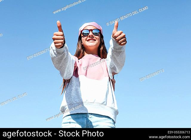 Girl woman with sunglasses and pink headscarf on her head, raising her thumbs, on October 19, International Breast Cancer Day, with the sky in the background