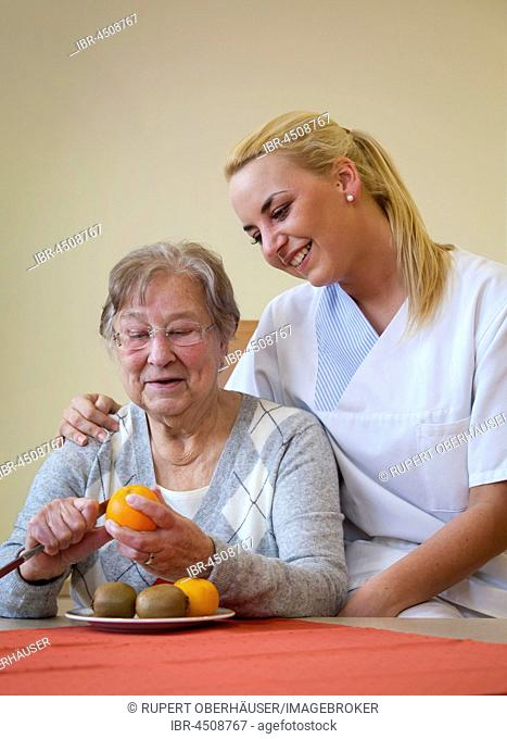 Nurse helping a senior citizen to peel fruit, Germany