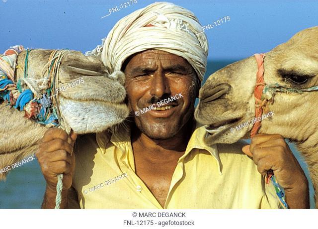 Man between two camels, mammals, Djerba, Tunisia, North Africa