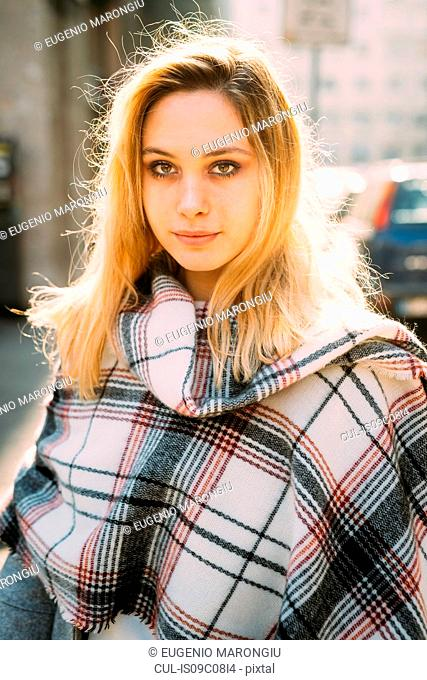 Young woman with long blond hair wrapped in shawl on city street
