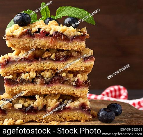 stack of square slices of baked crumble pie with blue plum on a wooden board, delicious dessert