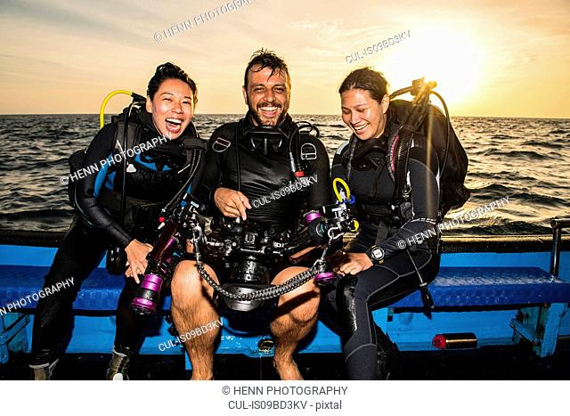 Friends looking at images on underwater camera after dive, Tubbataha Reefs Natural Park, Sulu Sea, Philippines