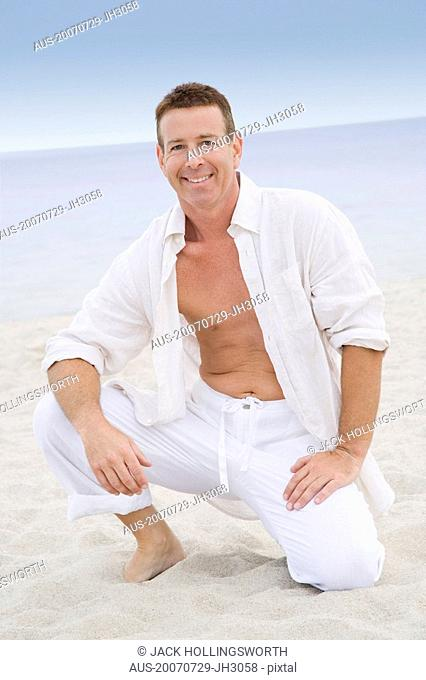 Portrait of a mature man kneeling on the beach and smiling