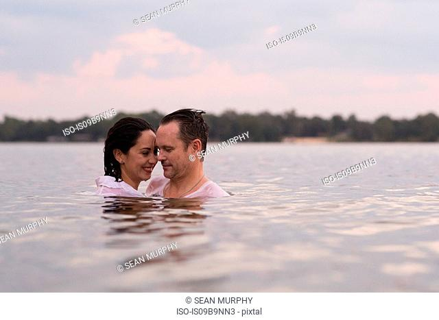 Clothed couple in water, Destin, Florida, United States, North America